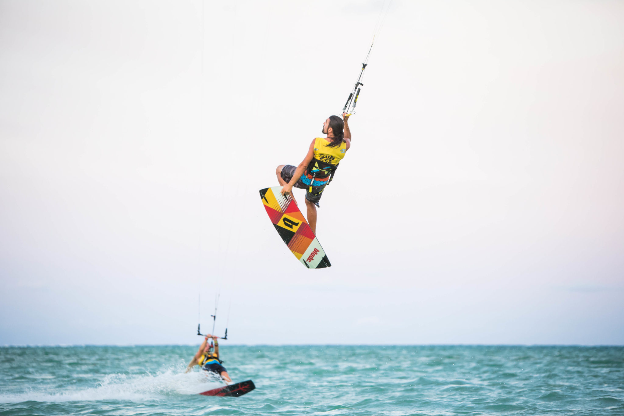 kitesurfer jumping and grabing the tail of the board in a paradise spot