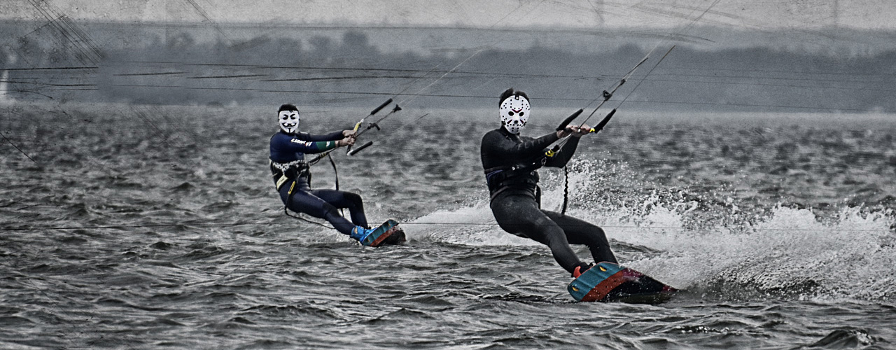 two kitesurfers riding in mask at dark and cloudy day